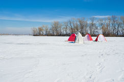 Winter landscape - fishermans' tents on a river Stock Image