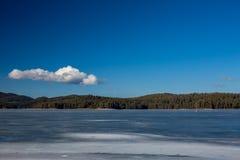 Winter landscape. Fishermen on frozen lake water, pine forest. Bulgaria, Rhodopes mountains, Shiroka Polyana lake. Stock Image