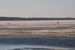 Winter landscape fishermen on the river ice fishing on a spring day stock image