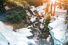 Winter landscape with forest stream. Snowy nature stock photography