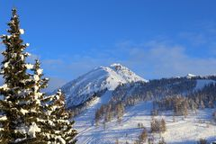 French Alps. Mountain peaks and ski slopes on snow-covered hill. Winter landscape in  French Alps. Mountain peaks and ski slopes on snow-covered hillside Royalty Free Stock Image