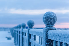 Winter landscape. Frosty morning, an iron chain on the embankment covered with a thick layer of frost. Stock Photos