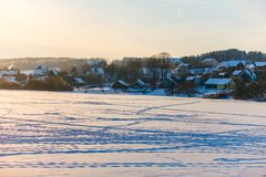 Winter landscape. Frozen lake covered with snow. Life in village stock image