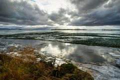 Winter Landscape frozen lake with ice floes and cloudy sky in Ic Stock Photography
