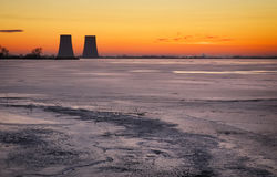 Winter landscape with frozen lake and power plant. Stock Photos