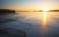 Winter landscape with frozen lake and sunset fiery sky. Royalty Free Stock Photo