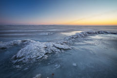 Winter landscape with frozen lake and sunset fiery sky. Stock Photos