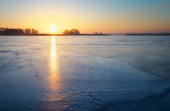 Winter landscape with frozen lake and sunset fiery sky. Royalty Free Stock Photos