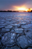Winter landscape with frozen lake and sunset sky. Royalty Free Stock Image