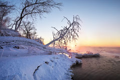 Winter landscape with frozen lake and sunset sky. Stock Photo