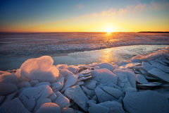 Winter landscape with frozen lake and sunset sky. Royalty Free Stock Photo