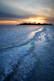Winter landscape with frozen lake and sunset sky. Stock Image