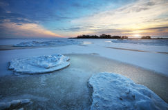 Winter landscape with frozen lake and sunset sky. Stock Photography