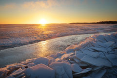 Winter landscape with frozen lake and sunset sky. Stock Photos
