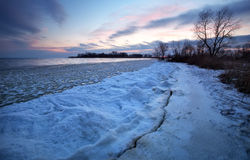 Winter landscape with frozen lake and sunset sky. Royalty Free Stock Images