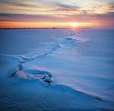 Winter landscape with frozen lake and sunset sky. Royalty Free Stock Photography