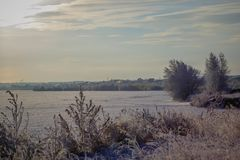 Winter landscape with frozen river and forest in the frost royalty free stock images