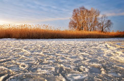 Winter landscape with frozen river and sunset sky Royalty Free Stock Image