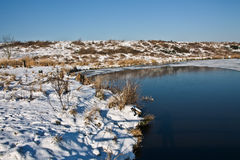 Winter landscape with half frozen pond. Royalty Free Stock Images