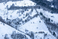 Winter landscape, hills with small cottages covered with snow Stock Photo