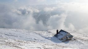 Winter landscape with a house on the mountain with haze and snow stock images