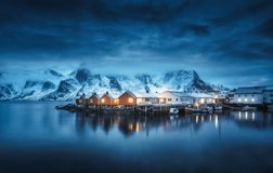 Winter landscape with houses, illumination, snowy mountains, sea. Blue cloudy sky reflected in water at night. Small fishing village with boats at twilight stock photography