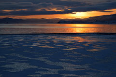 Winter landscape with ice formation process on lake at sunset. Combination of ice area covered with snow spots and smooth surface of water area Stock Photo