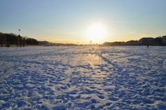 Winter landscape on the ice of the Neva river at sunset on a fro. Sty day in Saint-Petersburg royalty free stock image