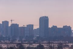Winter landscape industrial outskirts of the city. Silhouettes of buildings and cranes. Winter landscape industrial outskirts of the city. Silhouettes of royalty free stock image