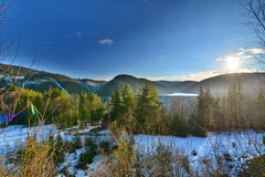 Winter landscape with lake, forest and sun. Stock Images