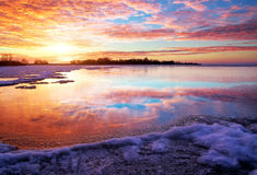 Winter landscape with lake and sunset fiery sky. Stock Images