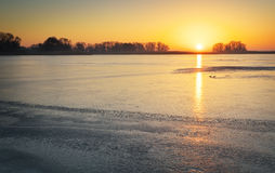 Winter landscape with lake and sunset fiery sky. Royalty Free Stock Photos