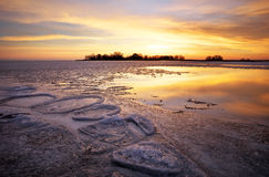 Winter landscape with lake and sunset sky. Royalty Free Stock Photo