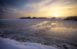 Winter landscape with lake and sunset sky. Stock Photography
