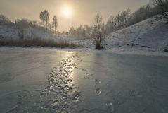 Winter landscape, the lake at sunset. Winter landscape, the lake at sunset, traces of man on ice Royalty Free Stock Photos