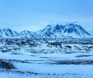 Winter  landscape with lava fields and  the snow capped mountains at dusk, Iceland.  near the Ring Road  Route 1 of Iceland, bet. Winter landscape with lava Royalty Free Stock Images