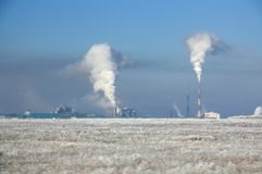 Winter landscape with metallurgical plant with heavy smoke from pipes behind a field covered with frozen dry grass under blue sky royalty free stock images