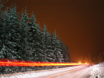 Winter landscape with motion blurred backlights. Winter landscape with motion blurred vehicle backlights at Kozara National Park near Prijedor, Bosnia and Royalty Free Stock Photos