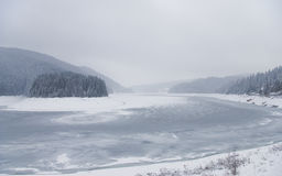 Winter landscape with mountain lake. Picture of a mountain lake in winter during snowfall, with fog Royalty Free Stock Photography