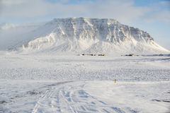Winter landscape with mountain, a lot of snow and small farm houses, Iceland Stock Photos