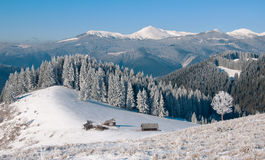 Winter landscape with a mountain valley. A wooden cross with a crucifix near the hut. Stock Image