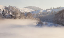 Winter landscape in the mountain village. Foggy mornin Royalty Free Stock Image