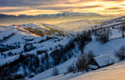 Winter landscape in mountainous rural area at sunrise. Village near the forest in mountainous area in winter carpathian landscapein morning light Stock Images