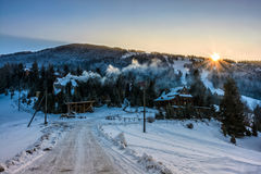 Winter landscape in mountainous rural area at sunset Stock Photos