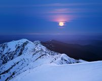 Winter landscape with a full moon in the mountains royalty free stock photo