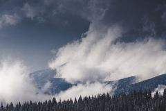 Winter Landscape in mountains. High mountains in clouds. Dramatic sky. View of snow-covered forest. stock photography