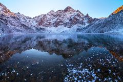 Winter landscape. Mountains reflected in frozen lake. Mountain lake covered with clear transparent ice. Winter natural background stock photo