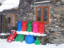 Winter landscape with multicolored sleds. Fairy winter landscape with multicolored sleds and rustic stone house Stock Photos