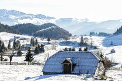 Winter landscape with and old house on the top of the mountain. stock image