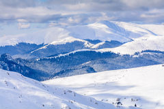 Winter landscape over Carpathian Mountains. Panorama of snow mou. Ntain range landscape with blue sky and white clouds from Carpathian Mountains Royalty Free Stock Photo